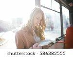 beautiful young woman sitting... | Shutterstock . vector #586382555