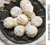 Small photo of Coconut biscuits with icing sugar over pewter plate and varied doilies