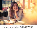 asian woman drinking coffee in... | Shutterstock . vector #586497056