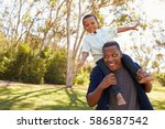 father carrying son on... | Shutterstock . vector #586587542