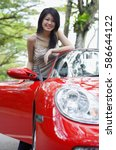 Woman standing next to red sports car