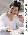mature woman in cafe holding... | Shutterstock . vector #586645148