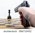 Small photo of hand with gun took aim at chess piece