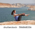 woman practicing yoga by lake | Shutterstock . vector #586868336