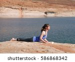 woman practicing yoga by lake | Shutterstock . vector #586868342
