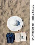 Small photo of Gela, Italy - 29.08.2016: abstract and conceptual summer, holidays at the beach. With a white hat, blue slippers flip-flops and a book with a lid on it. illustrative editorial