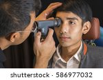doctor examining young asian... | Shutterstock . vector #586977032