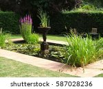 A Garden Pond With Statuary An...