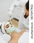 Small photo of Facial Skin Treatment. Ð¡loseup Of Beautiful Young Woman Receiving Cosmetic Mask In Beauty Salon. Beautician Applying Alginate Mask On Female Face With Smooth Soft Skin. Cosmetology. High Resolution