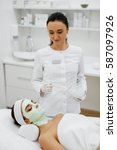 Small photo of Beauty Treatment. Closeup Of Beautician Applying Cosmetic Mask On Facial Skin Of Beautiful Healthy Young Woman. Female With Fresh Alginate Mask On Face Lying In Aesthetic Spa Salon. High Resolution