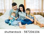 family posing on the bed in the ... | Shutterstock . vector #587206106