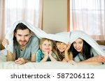 family posing on the bed in the ... | Shutterstock . vector #587206112