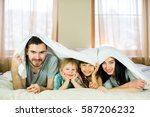 family posing on the bed in the ... | Shutterstock . vector #587206232