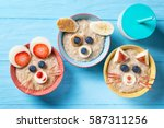 Stock photo funny bowls with oat porridge with cat dog and mouse faces made of fruits and berries food for 587311256