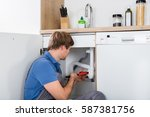 Small photo of Male Plumber Fixing Sink Pipe With Adjustable Wrench In Kitchen