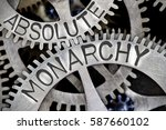 Small photo of Macro photo of tooth wheel mechanism with ABSOLUTE MONARCHY letters imprinted on metal surface