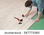 man installing new wooden... | Shutterstock . vector #587773385