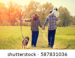 Stock photo happy family with dog walking on the rural dirt road on the field little girl sitting on dad s 587831036