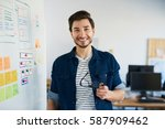 happy web developer standing in ... | Shutterstock . vector #587909462