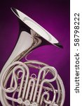 A professional double French horn isolated against a spotlight purple background. - stock photo