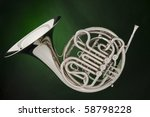 A professional double French horn isolated against a spotlight green background. - stock photo