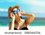 Small photo of Young female fashion model smiling and wearing big sunglasses on a beach, sun protection and skincare concept.