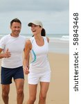couple jogging on a sandy beach | Shutterstock . vector #58843468