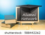 Small photo of Graduation hat, books, blackboard with text alumni network on a wooden background.