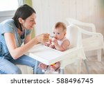 mum spoon feeds the child in... | Shutterstock . vector #588496745