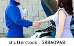 Caucasian young mechanic shaking hands with a female customer in front of a car - stock photo
