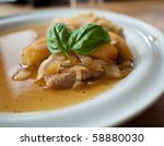 Pork with basil on top on a nice white plate - stock photo