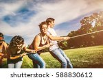 happy friends pulling rope and... | Shutterstock . vector #588830612