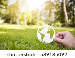 Small photo of Environment concept, paper globe on the grass with hands, blur