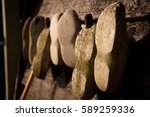 Small photo of Closeup antique traditional old Dutch Netherlands Holland wooden clog shoes time weathered and worn hole hanging on outdoor black wall in morning sunlight in bright yellow light in travel tour scene