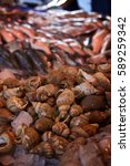 Small photo of Abundant catch of fresh seafood at European monger stall at farmers market on ice with pile of wet snail shells in foreground and stacks of small and medium sized whole fish in background in shade