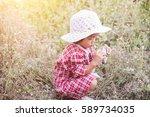 little girl photographs flower... | Shutterstock . vector #589734035
