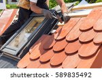 hands of roofer laying tile on... | Shutterstock . vector #589835492