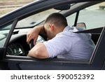 attention tired man driving car | Shutterstock . vector #590052392