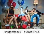 Small photo of Two beautiful girls relaxing on sofa after New Year party while their drunken male friends having nap, all floor covered with confetti