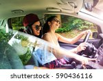 two young female on car trip... | Shutterstock . vector #590436116