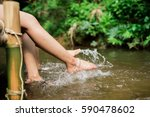 foots in the water in natural... | Shutterstock . vector #590478602