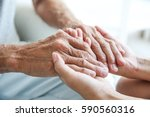 young woman holding senior man... | Shutterstock . vector #590560316