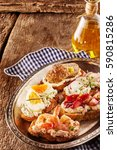 Small photo of Tasty canapes in a rustic pub or restaurant on toasted baguette topped with quark cheese and prawns, egg, strawberries, meatballs and radish seasoned with fresh herbs