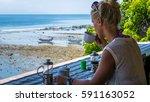 Small photo of Women Morning Coffee near Seaweed Plantations algal, fisherman boats in background - Nusa Penida, Bali, Indonesia