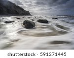 stones on coast at moving sea ... | Shutterstock . vector #591271445