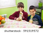two boys drinking smoothie in... | Shutterstock . vector #591519572
