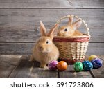 Stock photo rabbits with easter eggs on wooden background 591723806