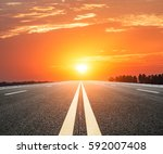 asphalt road and sky at sunset | Shutterstock . vector #592007408