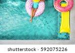 woman relaxing on donut lilo in ... | Shutterstock . vector #592075226