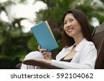 woman sitting outdoors  reading ... | Shutterstock . vector #592104062